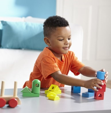 boy playing with melissa and doug wooden stacking train
