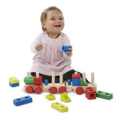 toddler playing with melissa and doug stacking train pieces