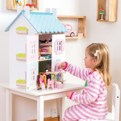 kid plsying with dolls from pink doll house