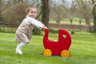 girl pushing moover wooden dolls pram red