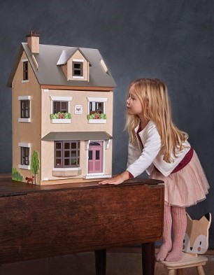 standing on stool to look doll house