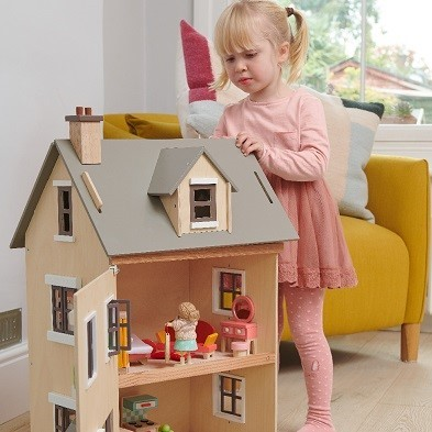 kid playing with big doll house