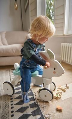 child on wooden rabbit bike
