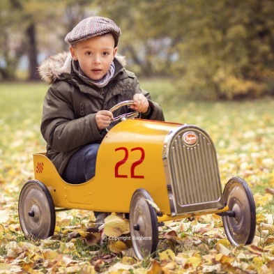kid riding yellow vintage car